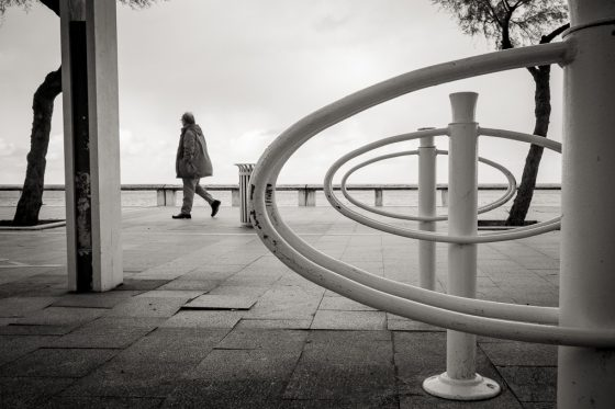 Arcachon, un homme se promène sur la promenade face à la mer.
