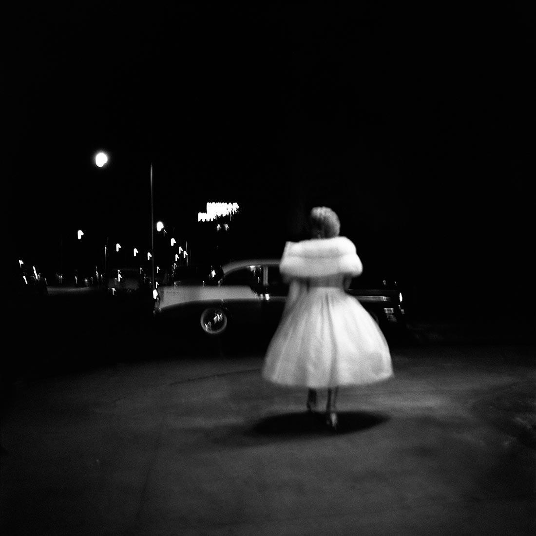 Une femme de blanc vêtue retourne à sa voiture. Photo de Vivian Maier