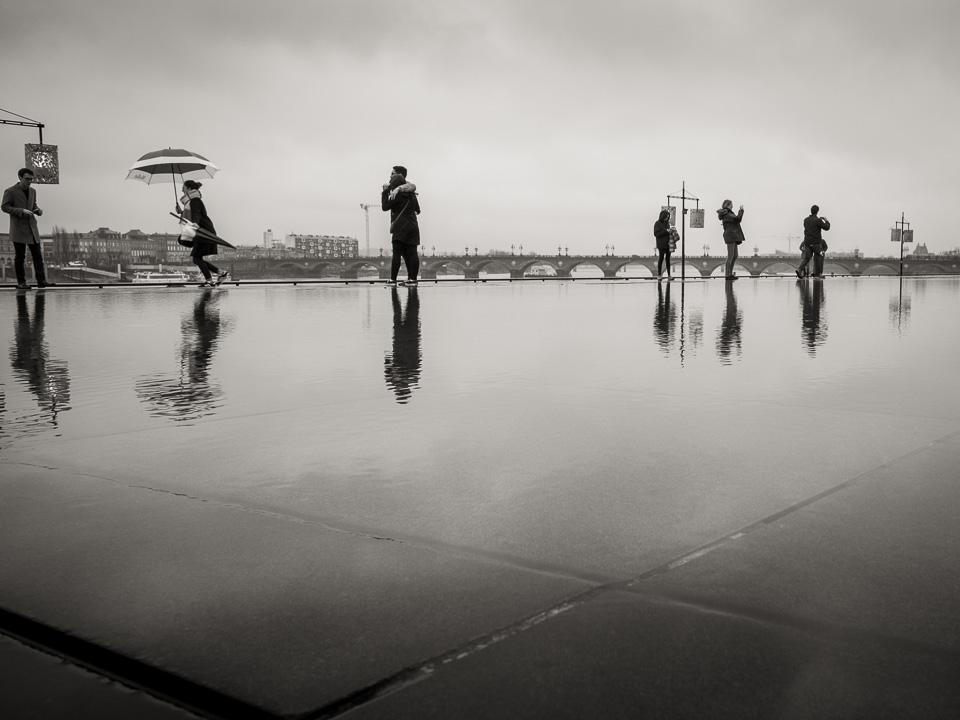 Une jeune femme court sur le miroir d'eau avec un parapluie