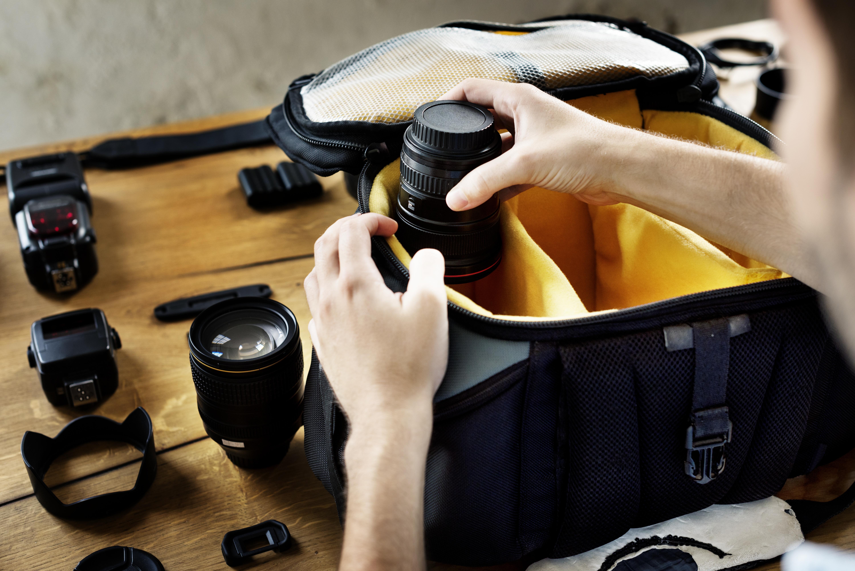 Man packing camera lens to his bag